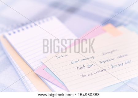 Turkish; Learning New Language Writing Greetings On The Notebook