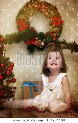 vintage effect on photo cute little girl dresses up Christmas tree on the floor in the room