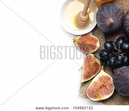 ripe figs, grapes and honey on a white background