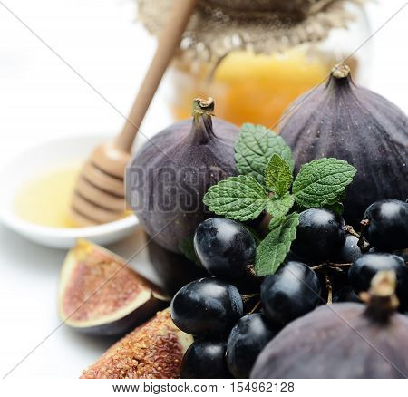 mint, figs, grapes and honey on a white background