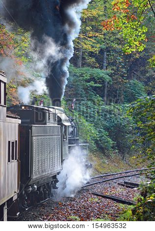 Black smoke billowing from a steam train in the fall.