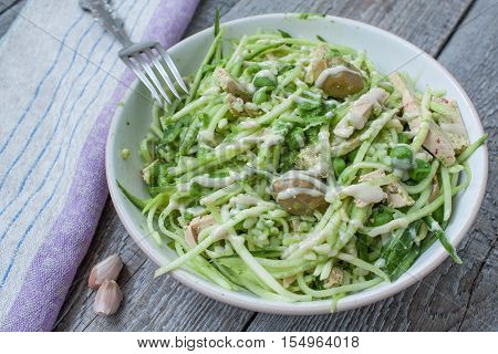 vegan zucchini pasta with tofu, bulgur, green peas, olives and pesto of parsley in a jar. vegetables every day for your health!