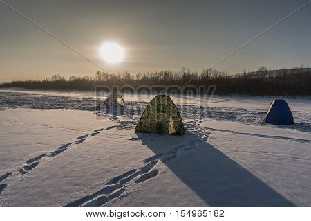 Winter fishing on the river in the evening