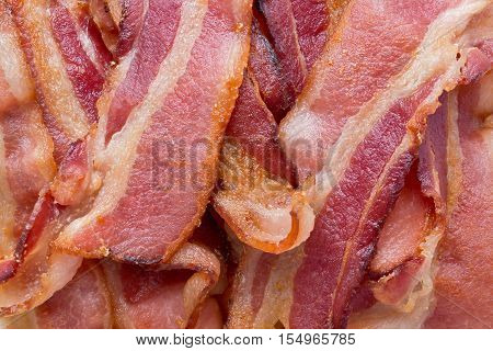 Background texture of several fried bacon strips.