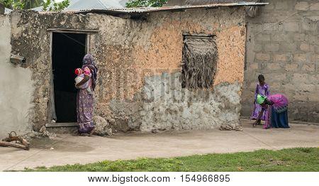 ZANZIBAR, TANZANIYA- JULY 15: african woman with baby in her hands near old house in Zanzibar village on July 15, 2016 in Zanzibar