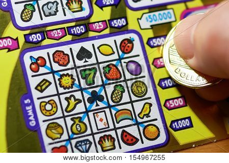 Coquitlam BC Canada - October 31, 2016 : Man scratching lottery ticket. The British Columbia Lottery Corporation has provided government sanctioned lottery games in British Columbia since 1985.