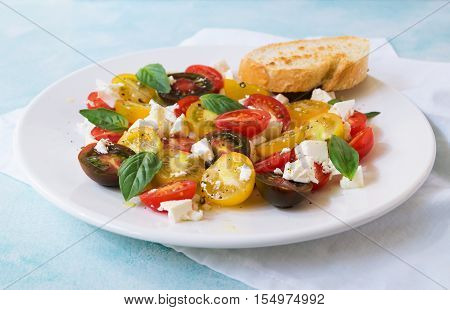 Summer heirloom tomato salad with fresh feta cheese on white plate on blue background selective focus horizontal