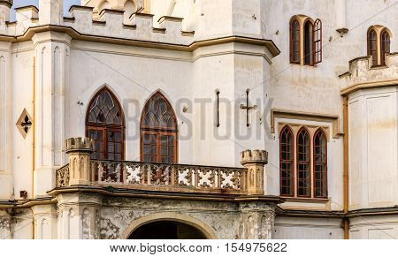 Detail of facade with balcony and windows of abandoned and seedy neogothic mansion in Rusovce near Bratislava Slovakia.