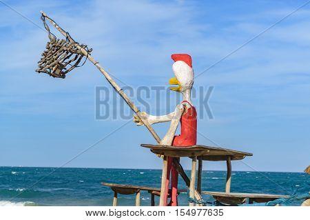 Funny chicken sculpture fishing at beach in Porto Galinhas Pernambuco Brazil