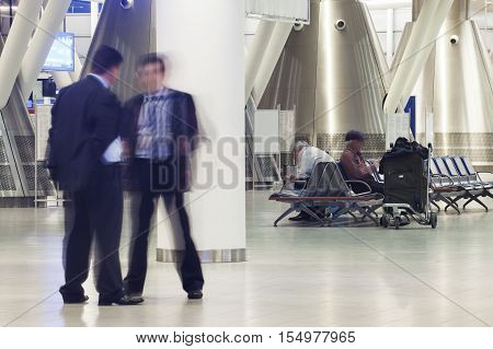 A few blurred figures of waiting passengers in a modern airport or train station terminal.