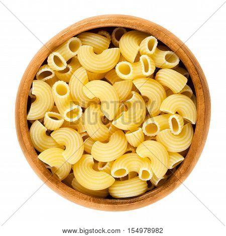 Chifferi pasta in wooden bowl. Bent tubes, short-cut and wide macaroni. Italian noodles prepared with eggs. Uncooked dried durum wheat semolina pasta. Isolated macro food photo over white background.