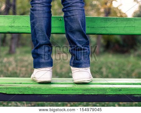 man wearing jeans and white sneakers is standing on green bench