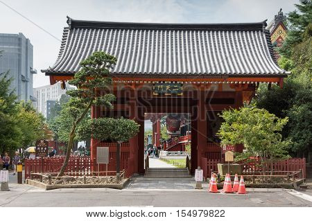 Tokyo Japan - September 26 2016: The vermilion Nitenmon Gate of Senso-ji Buddhist Temple in Tokyo. Eastern Entrance. People and part of Honzo hall visible. Light blue sky some green foliage.