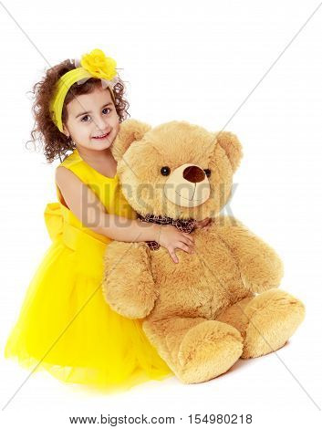 Joyful little girl in a yellow dress and bow on her head sitting on the floor. Girl hugging a big Teddy bear.Isolated on white background.