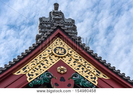 Tokyo Japan - September 26 2016: Closeup of highly gold vermilion and gray decorated top of Honzo hall at Senso-ji Buddhist Temple. Against blue cloudy sky.