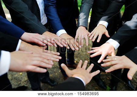 Groomsmen showing their hands at wedding on summer day
