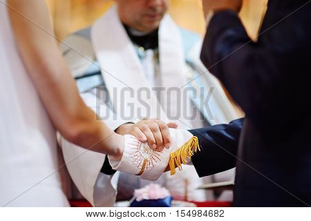 Bride And Groom's Hands Wrapped In Priest's Cassock