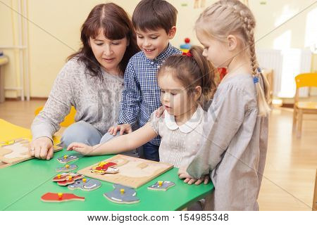 beautiful mature woman teacher collect puzzle with three pupils of a kindergarten classroom at the green table. Horizontal color image.