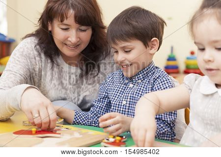 beautiful mature caucasian female teacher collects the puzzle with a pupil a boy of preschool age. In the classroom at the green table.