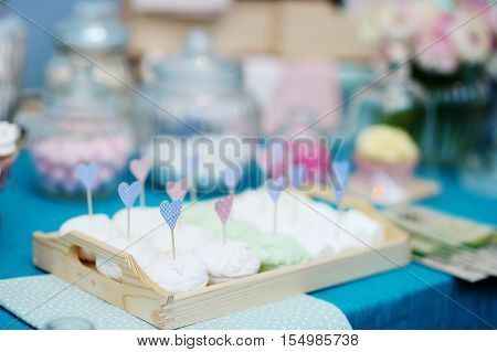 Delicious wedding marshmallows with heart-shaped sticks on a table
