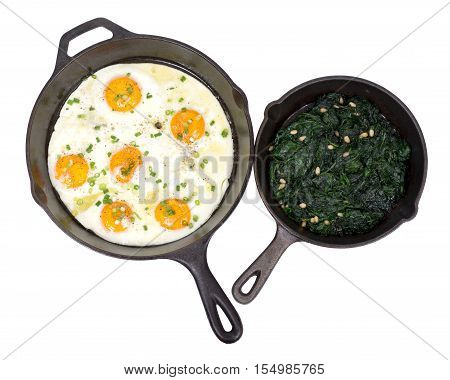 Fried eggs and sauteed spinach on cast iron skillet isolated on white background