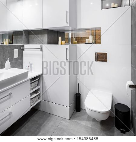 White high-gloss bathroom with functional furniture and grey flooring