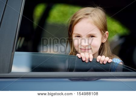 A Little Girl Is Sticking Her Head Out The Car Window