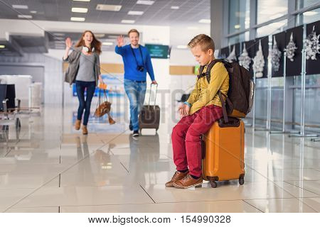 Son, we are here. Upset cute boy sitting on baggage at airport with his parents walking to him on background