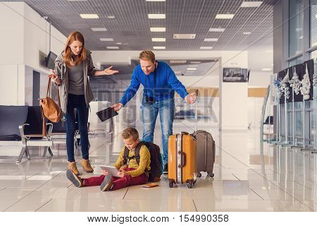 You can not sit on floor. Little boy sitting on floor at airport and playing with digital tablet with indignant parents near him