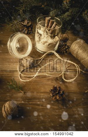 Original idea for a Christmas gift: a set of dry ingredients for ginger cookies, decorated in a jar, on a background of branches of the fir, cones, nuts. Copy space, vintage, toned