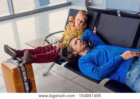 Like father like son. Top view shot of father and son sleeping in airport lounge while waiting for their flight