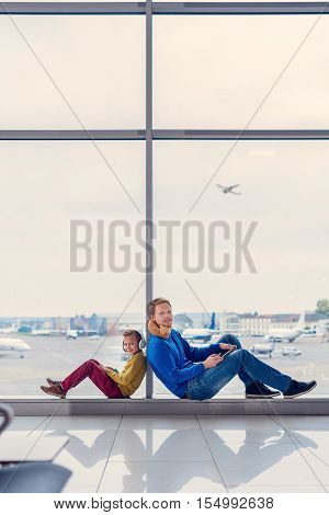 Our first trip together. Smiling young father and his little son sitting on windowsill in airport lounge and looking at camera