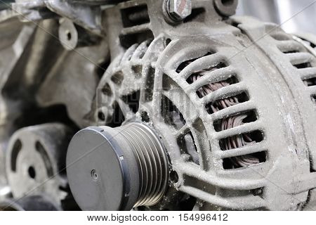 Part of a car engine with the image of an electric generator