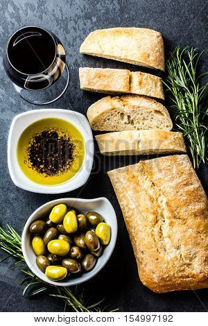Bread ciabatta, olives, arugula, olive pepper oil, olives, rurosemary and glass of red wine on stone slate black background. Top view copy space
