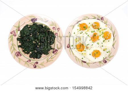 Fried eggs and sauteed spinach on ceramic plate isolated on white background