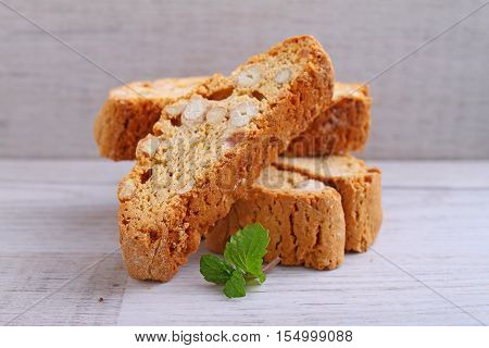 Biscotti with nuts on a wooden background decorated with leaves mint. selective focus
