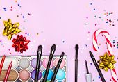 Makeup for festive party. Color glitter eyeshadow, mascara, eyeliner, lip liners, lip gloss, makeup brushes and applicator with candy cane, gift wrap bows and confetti on pink background. Copy space poster