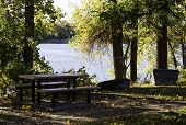 Idyllic landscape scene with picnic table, trees and lake view in Laval QC on a bright sunny cloudless day in October. poster