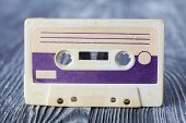 Violet compact cassette with magnetic tape recording format for audio recording and playback. MC on gray wooden background. poster
