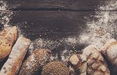 Bread border on dark wood with copy space background. Brown and white whole grain loaves still life composition with wheat flour sprinkled around. Bakery, cooking and grocery store concept. poster
