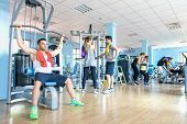 Small group of sportive friends at gym fitness club center - Happy sporty people interacting in weight room training - Social gathering concept in sport lifestyle context - Main focus in middle frame poster