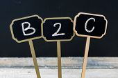 Business acronym B2C as Business To Consumer written with chalk on wooden mini blackboard labels defocused chalkboard and wood table in background poster