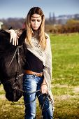 young blond woman on green field with horse poster