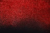Red glitter sand texture on black, abstract background. Red dusty shimmer decoration, shiny and sparkling. Holidays and glamour concept. poster