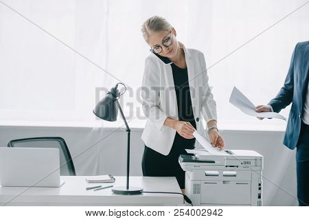 Businesswoman Talking On Smartphone While Using Printer In Office With Colleague Near By