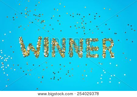 The Word Winner Is Laid Out Of Starry Confetti On A Blue Background.