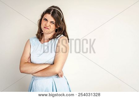 A Beautiful Pouted And Capricious Caucasian Brunette Girl With Crossed Hands Making Unhappy Faces. R