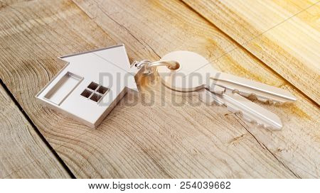 House as a pendant on a key on wooden table as a house purchase and housing concept (3d rendering)