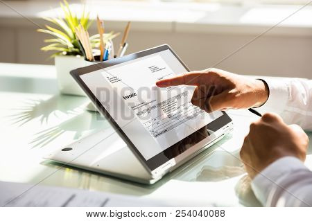 Businessman Examining Invoice On Laptop