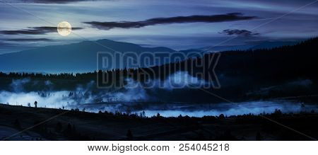 Panorama Of Countryside At Night In Full Moon Light. Beautiful Landscape In Mountains With Fog Risin